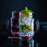 Fresh berries with ice in mason jar on dark background. Detox diet.