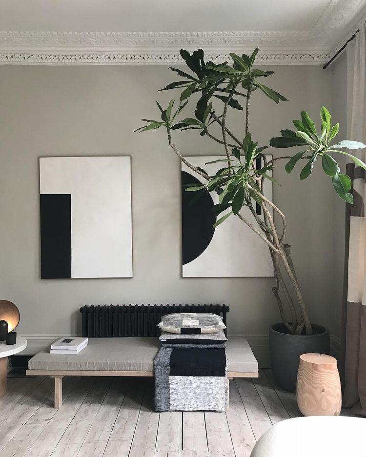 day bed styled with a big plant and black and white art