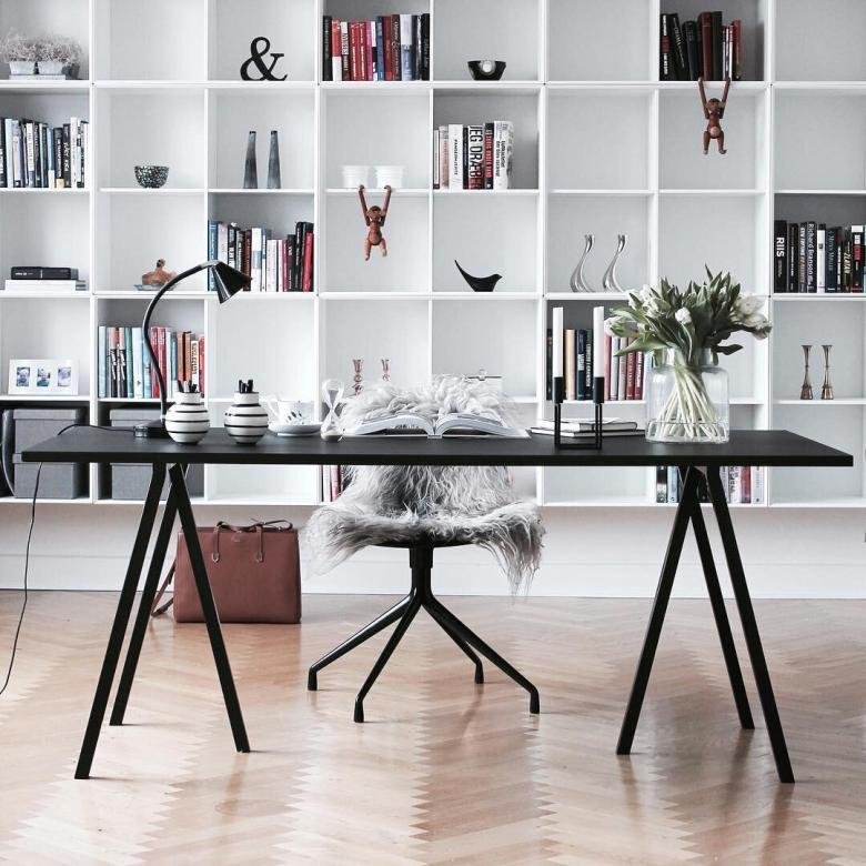 beautiful home office with large open shelves and black desk