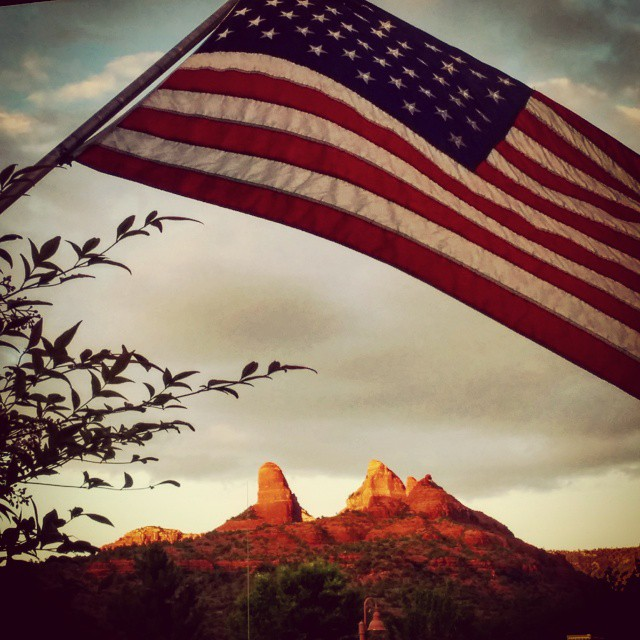 The flag flies over Sedona's red rocks.