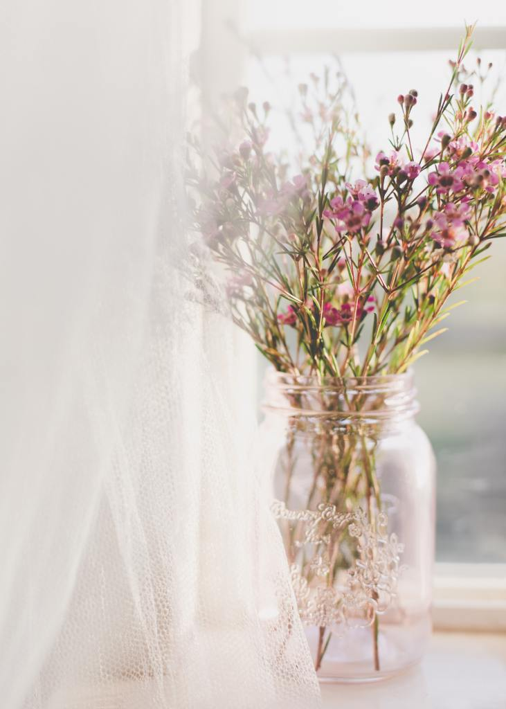 Spring flowers in a jar on a table.