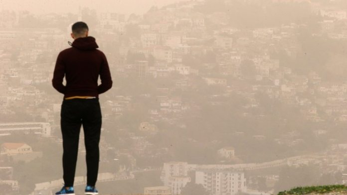 In Algiers, Algeria, a man looks out over the city that is shrouded in Sahara dust (Photo: Fateh Guidoum / AP)
