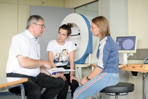 Fachschülerinnen zusammen mit einer Lehrkraft bei der Auswertung und Besprechung einer Perimetrie (Gesichtsfeldmessung).