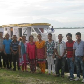 Jorhat Boat Clinic staff, members from PMU, Guwahati pose with the now repaired Nahor as backdrop