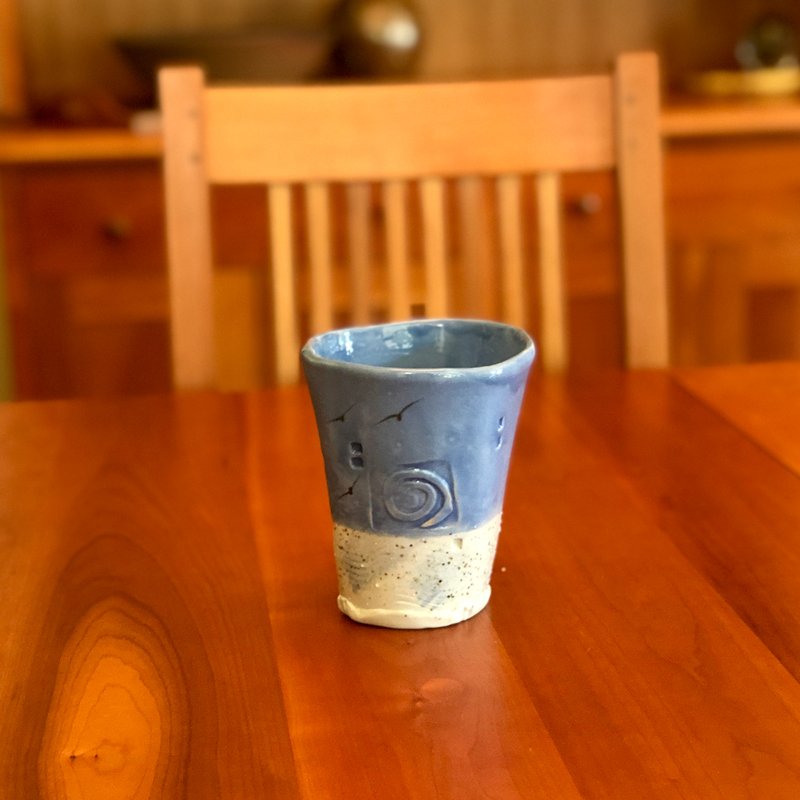 handmade ceramic tumbler with blue glaze and beach sand