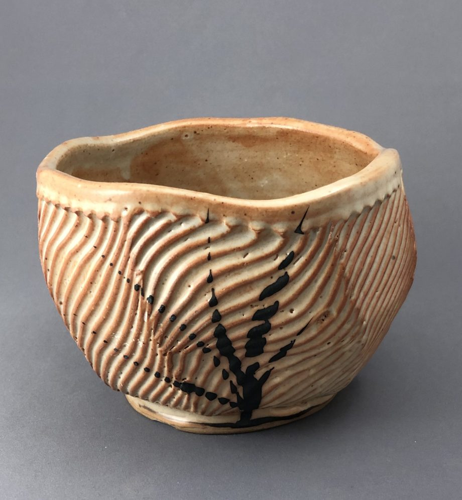 handmade bowl with lines carved through the clay