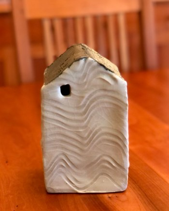 handmade decorative ceramic house with waves carved through it