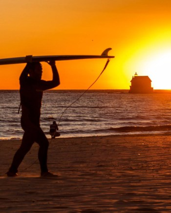 photograph of surfer at sunset with grand haven pier in background