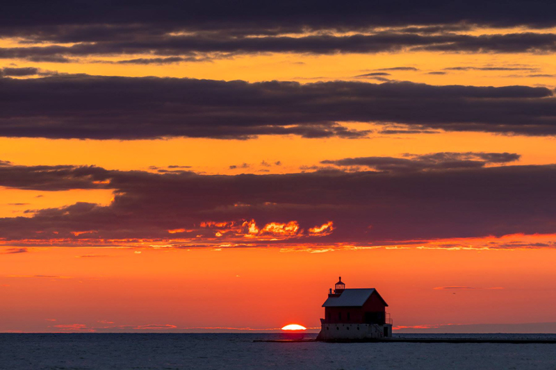 photograph of the grand haven lighthouse at sunset