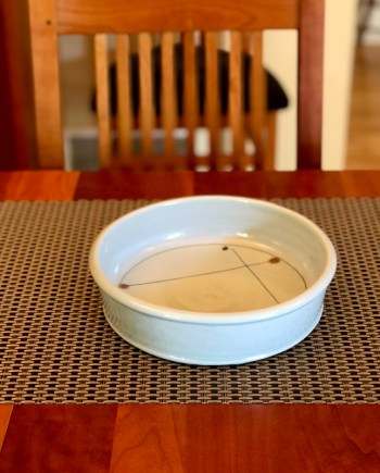 round handmade ceramic bake dish on a table