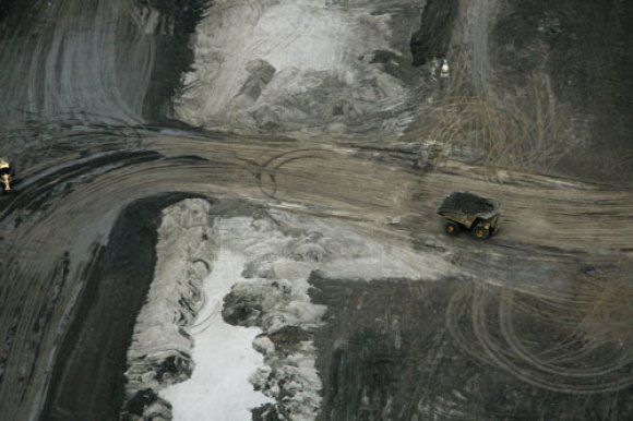 A giant earth mover transports earth mined at an open pit for processing to separate the bitumen.  © Greenpeace / Eamon Mac Mahon