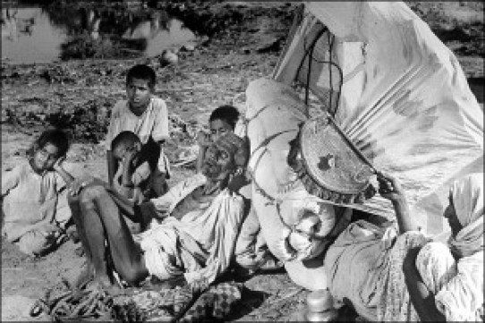 """An aged and abandoned Muslim couple and their grand children sitting by the the roadside on this arduous journey. """"The old man is dying of exhaustion. The caravan has gone on,"""" wrote Bourke-White. © BBC."""