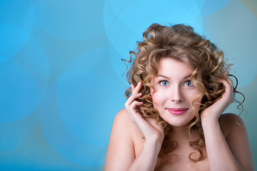 Portrait of a curly haired woman on a blue background close-up. Hair and make-up.
