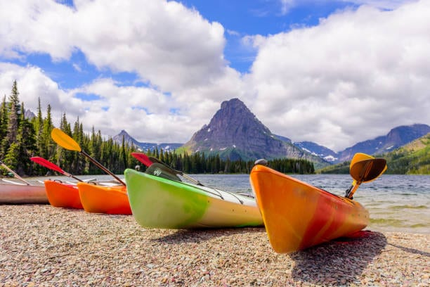 Several canoes lakeside with a great mountain view