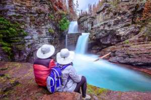 Glacier national park a couple looking at water falls best bed & breakfast in montana wedding venue best hotel near kalispell