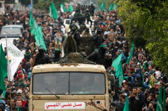 Palestinian members of al-Qassam Brigades display a home-made rocket during a military parade in Gaza City