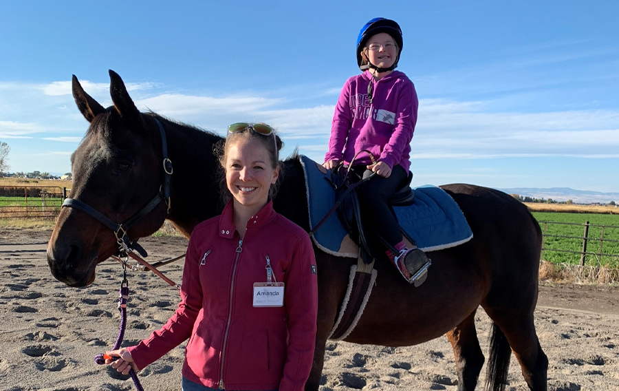 I started working within the Equine Therapeutic Riding Program at Eagle Mount the summer of 2018. I have been involved with the equine industry my entire life, but this was my first experience working within the therapy sector. I assist as a horse leader to ensure that the horse responds appropriately when the rider is working on their skills. I also get to interact with students while helping with grooming and tacking, as well as any pick up help around the barn.