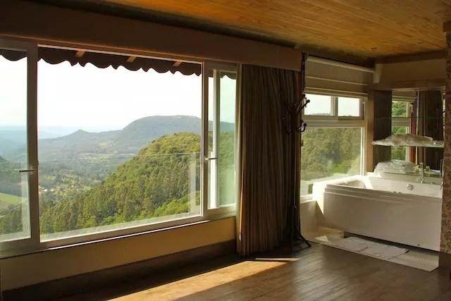 quarto com banheira e cama de frente para a vista do Vale