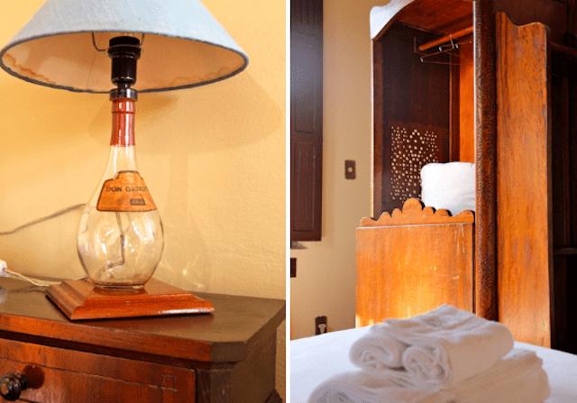 detalhes do quarto: o abajur com uma das garrafas clássicas de vinícola e o confessionário dentro do quarto