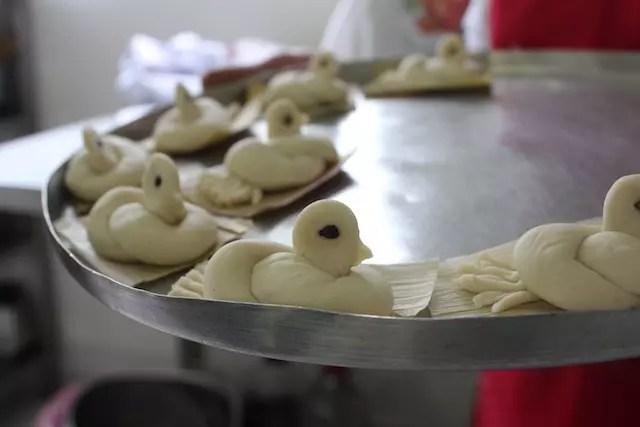 os pães em formatos de pomba prontos para irem ao forno