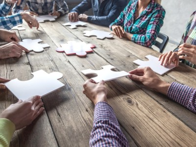 Business people and puzzle pieces on wooden table, teamwork concept