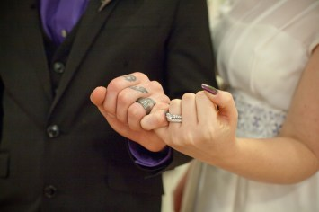 The bride and groom show off their wedding rings