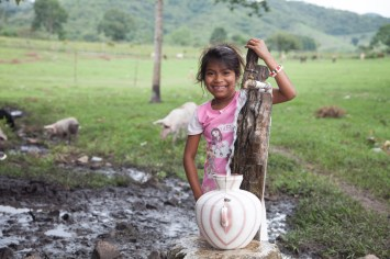 A young girl gathers water from the single spigot in San Jose de las Lagrimas, Guatemala