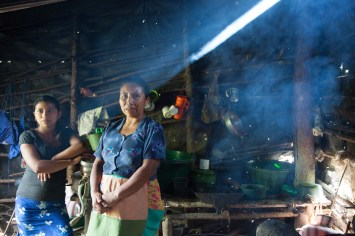 A mother and daughter inside their smokey house in San Jose de las Lagrimas, Guatemala