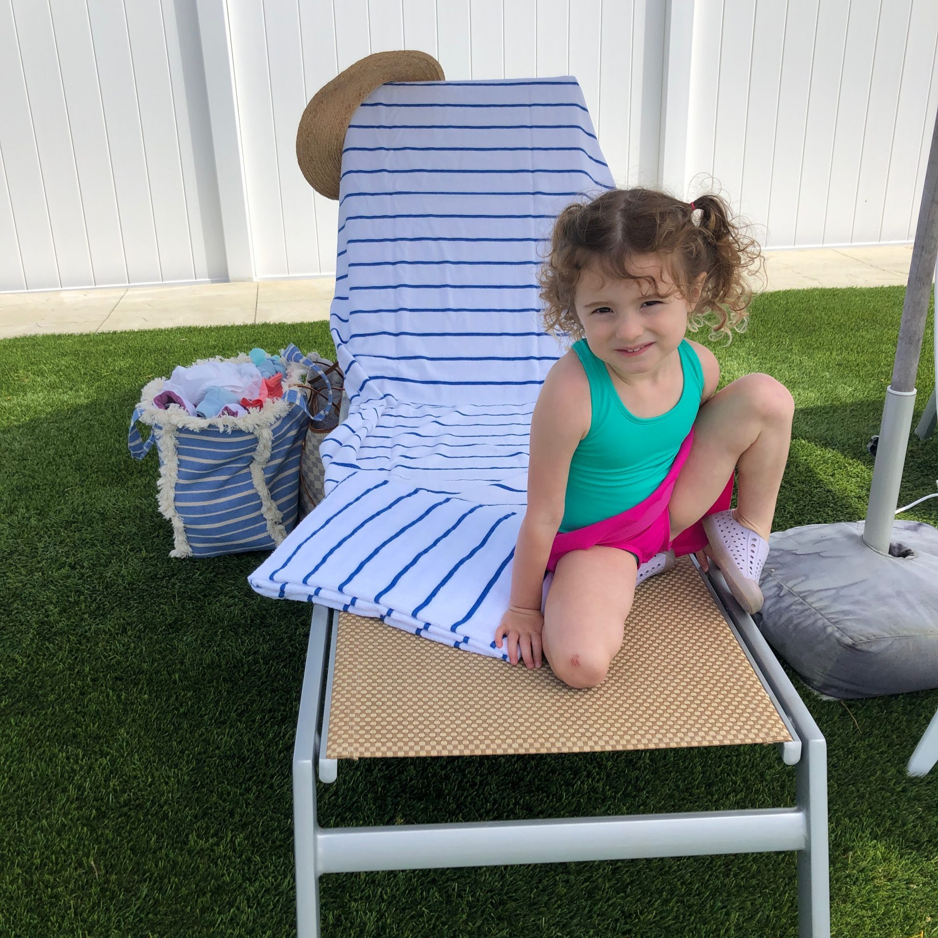 little girl sitting on pool chair