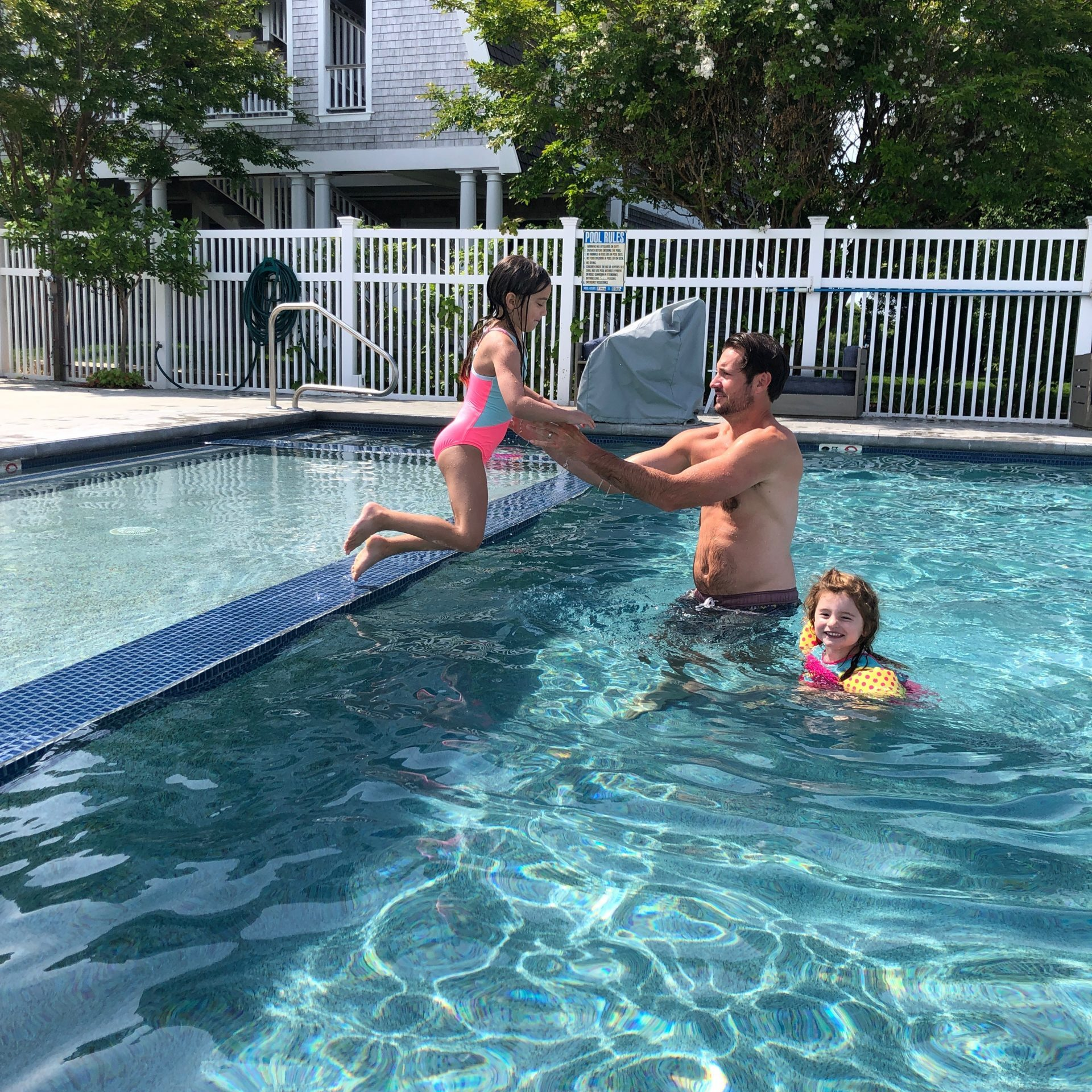 little girl jumping to dad in pool