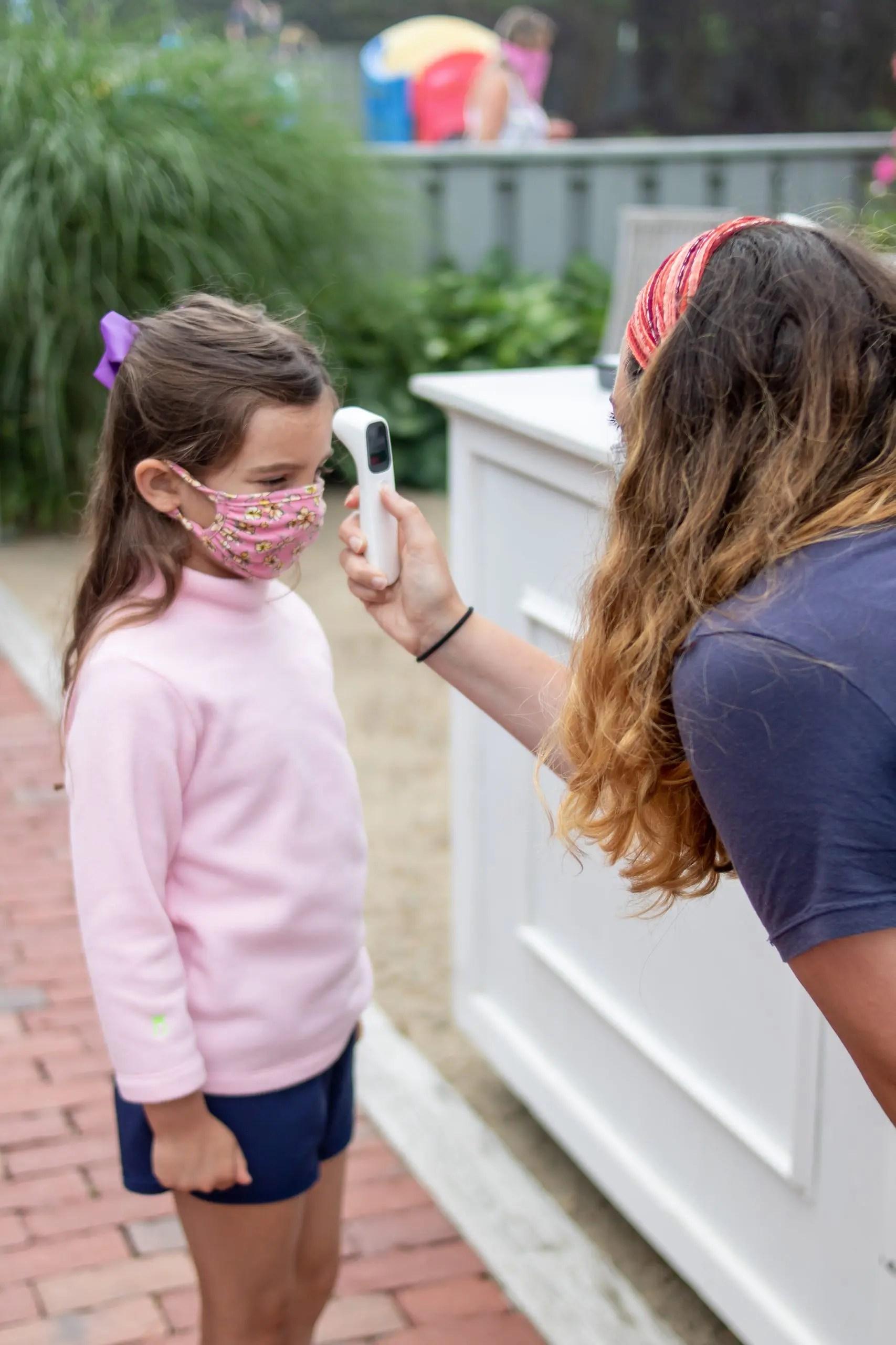 little girl wearing mask having temperature read