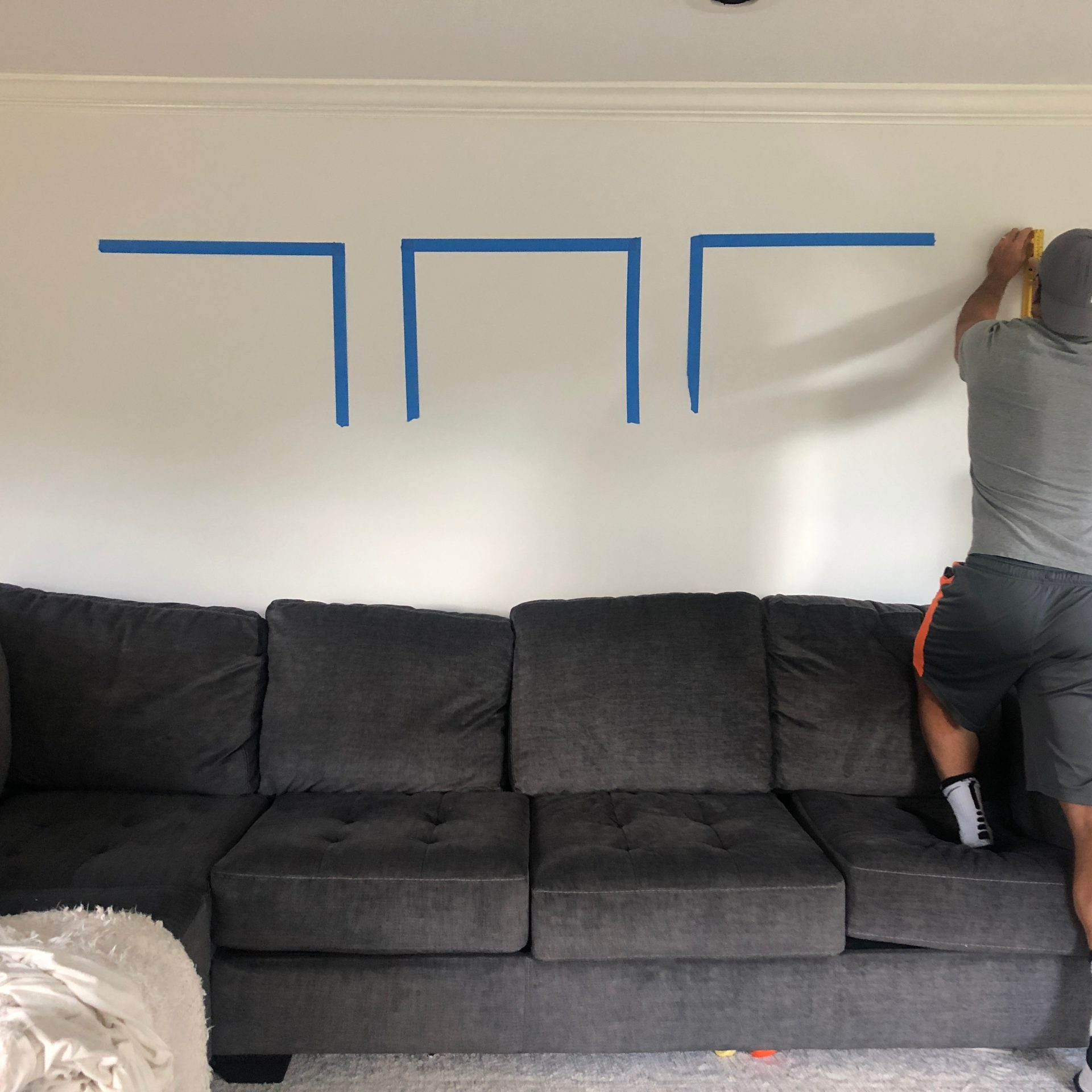 man spacing out painters tape on wall for prints