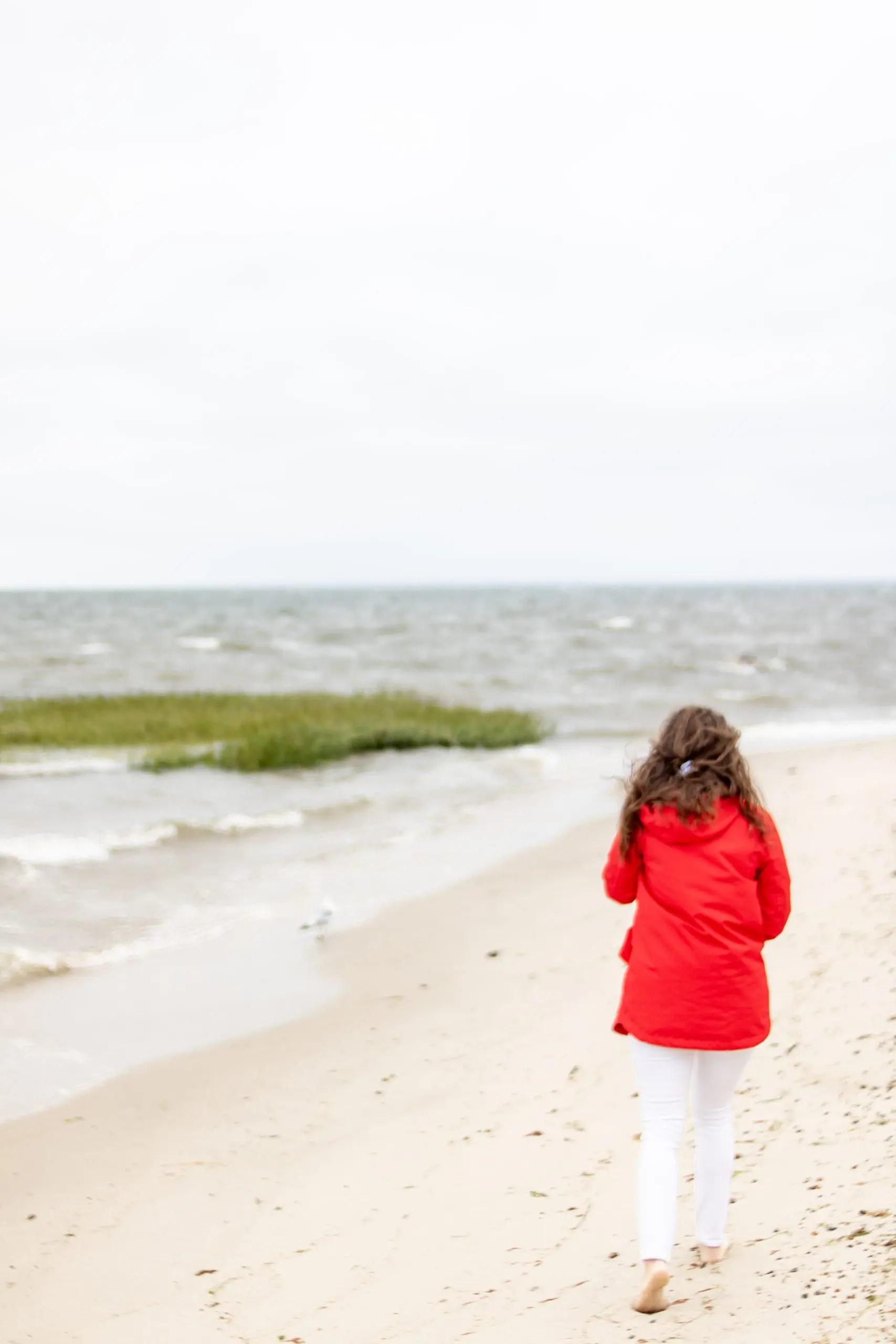 woman walking in red raincoat on Breakwater Beach Brewster Ma