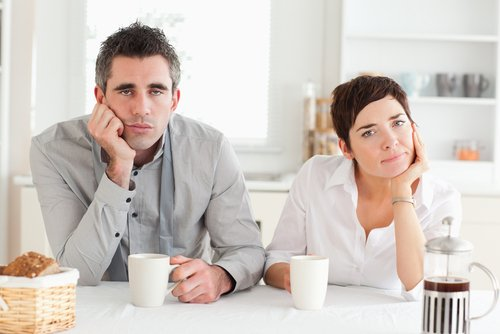 tired looking couple drinking coffee