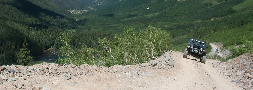 View of a jeep climbing narrow trail East to the top of Ophir Pass, Colorado