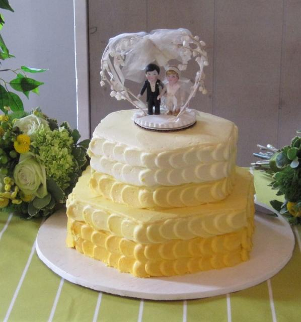 Two Tier Hexagonal Yellow And Cream Wedding Cake With Doll