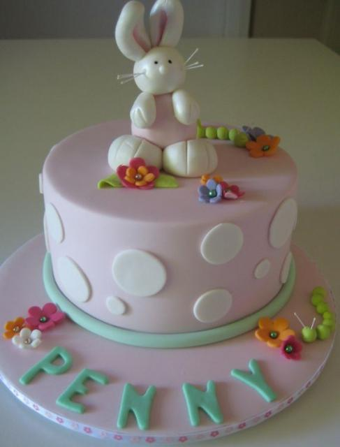 Light Pink First Birthday Cake With Bunny Rabbit On Top