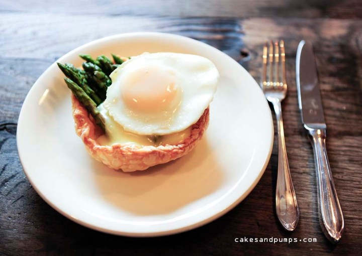Little pie on the table with green asparagus, hollandaise sauce and a little egg