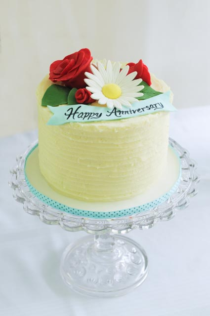 Buttercream anniversary cake with roses and daisies