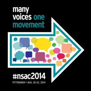 "nsac logo: on black background it says ""many voices"" in white and ""one movement"" in teal.  There is a large arrow filled with speech bubbles pointing to the right."