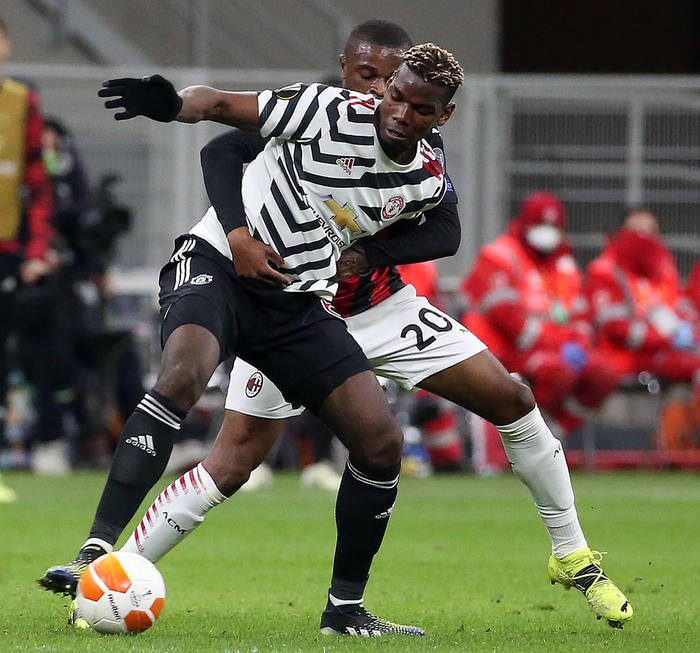 Manchester United's Paul Pogba  (L)  challenges for the ball  AC Milan's Pierre Kalulu during the UEFA Europa League round of 16 second leg soccer match between AC Milan and Manchester United at Giuseppe Meazza stadium in Milan, Italy, 18 March 2021. ANSA/MATTEO BAZZI