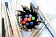 Coloured pencils and paint brushes
