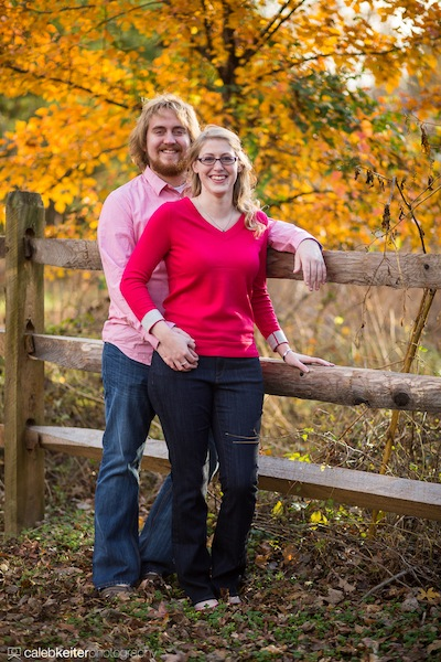 A couple have their portrait taken next to a wooden fence and colorful tree during fall near Richmond, VA