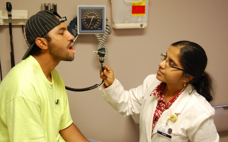 Patient Baldemar Sanchez is examined for mouth blisters by Dr. Suchitra Rao at the Golden Valley Health Center in Merced. A Spanish translator helped Sanchez communicate with Rao