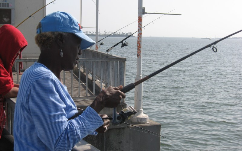 Deborah White of Fontana fishes on a recent Saturday afternoon at the Belmont Veterans Memorial Pier in Long Beach. Outreach programs have helped White and other anglers learn about the dangers of contaminated fish.