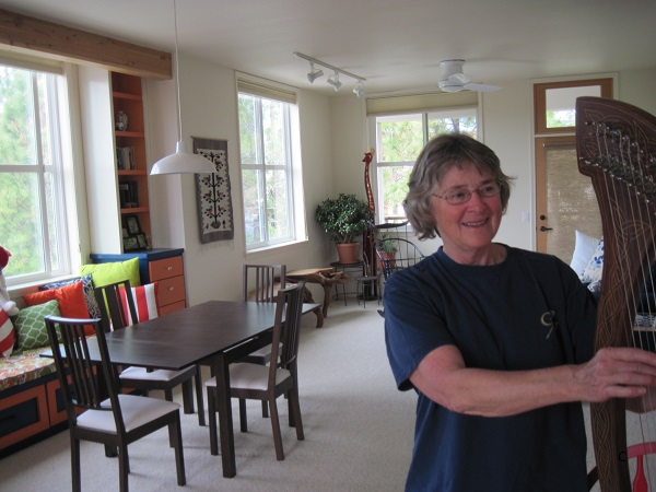 Claire Miller playing the harp in her Wolf Creek Lodge cohousing home.
