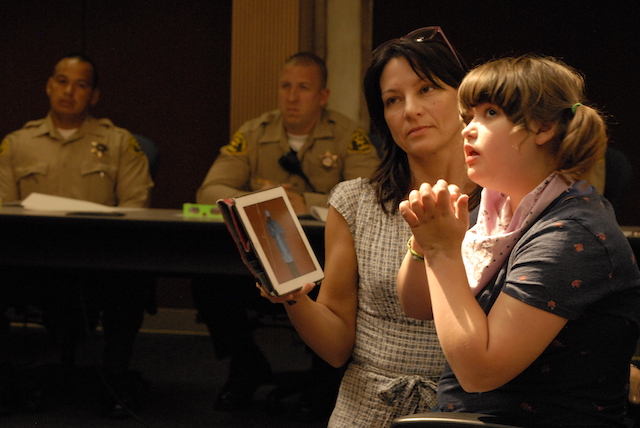 Bobbie Hendrickson brought her 14-year-old daughter, Sydney, to a recent Los Angeles County Sheriff's Department seminar on interactions with the autistic. Sydney, who is autistic, sometimes relies on her computer tablet to communicate with her family. The programs Sydney watches on it can help her calm down when she is upset, Bobbie Hendrickson says. At the seminar, she urged sheriff's deputies to defer to the parents and caregivers of autistic persons for guidance in keeping interactions with law enforcement orderly and calm. Photo: Chris Richard