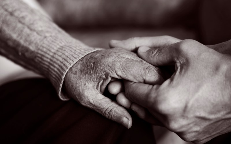 Closeup of a young man holding the hand of an old woman with affection.