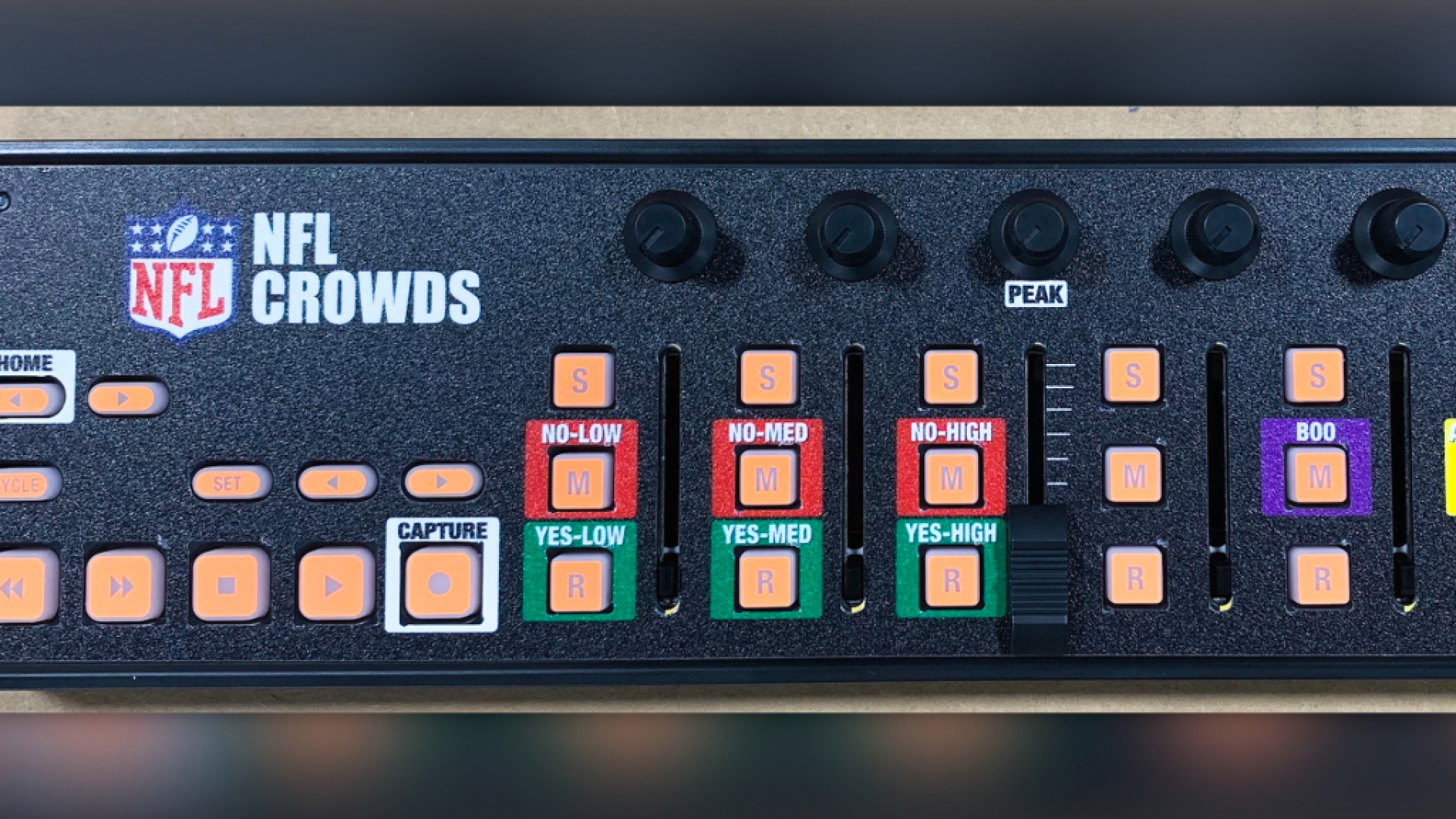 """Closeup of a button controller that says """"NFL Crowds"""" on it, and has a cluster of red and green buttons labeled Yes/No, Low/Med/High"""