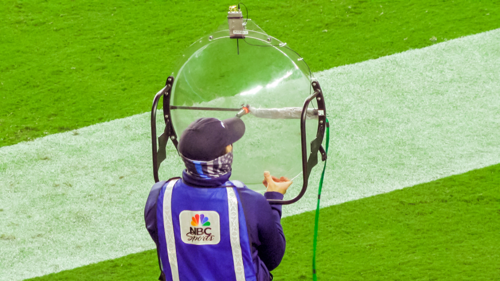 A man in an NBC Sports vest holds a large clear dish-shaped microphone